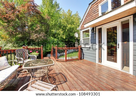 House exterior with large open deck and outdoor furniture. - stock photo