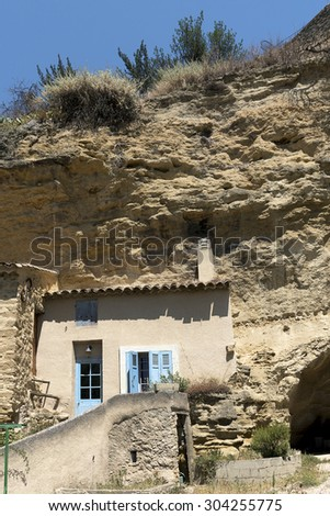 House facade in front of a cave in the mountain in the old village of Cadenet, Provence, south France, Luberon Massif, vertical - stock photo