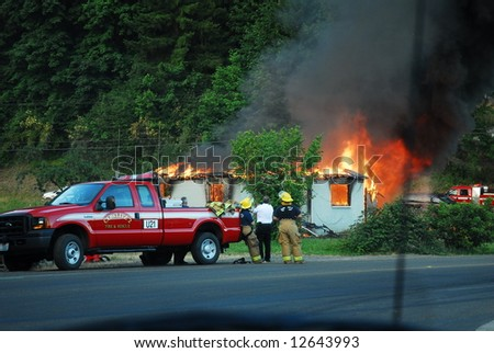 House fire with a group of firefighters getting their photo taken in front of the fire. - stock photo