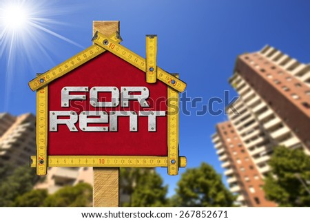 House For Rent Sign - Wooden Meter. Yellow wooden meter ruler in the shape of house with text for rent. For rent real estate sign with tall and blurred buildings in the background - stock photo