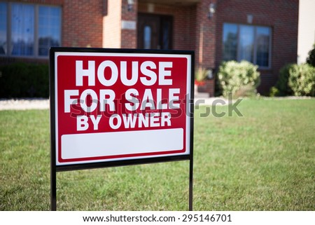 House For Sale By Owner Sign in a front yard of a house - stock photo