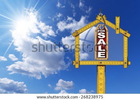 House For Sale Sign - Wooden Meter. Yellow wooden meter ruler in the shape of house and label with text for sale. For sale real estate sign on blue sky with clouds and sun rays  - stock photo