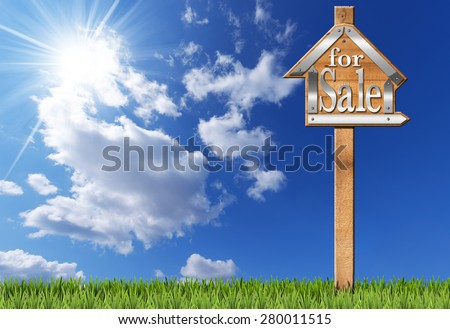 House For Sale - Wooden Sign with Pole. Wooden and metallic sign in the shape of house with text for sale and wooden pole. For sale real estate sign on blue sky with clouds, sun rays and green grass - stock photo