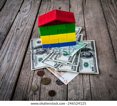 House from the paper and money on wooden background - stock photo