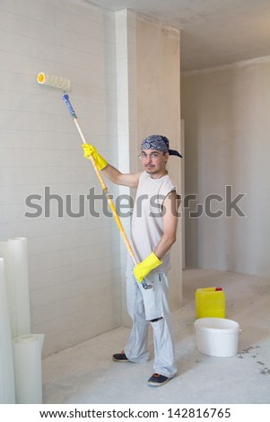 House improvement. Young man painting wallpaper with painting roller - stock photo