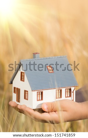 House in children`s hands against autumn yellow background. Real estate concept - stock photo