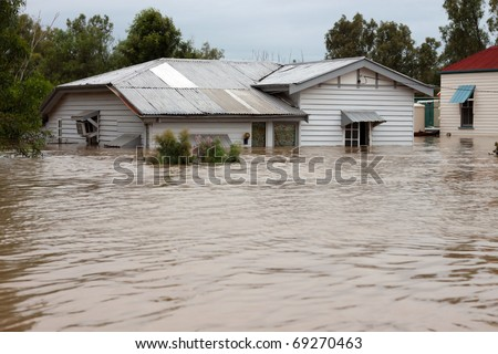 House in floodwater.  Traditional timber country home with water up the windows.  Ideal for insurance or disaster illustration. - stock photo