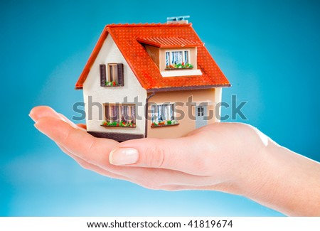 house in human hands on the blue - stock photo