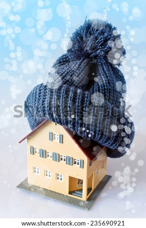 house in winter - heating system concept and cold snowy weather with model of a house wearing a knitted cap - stock photo