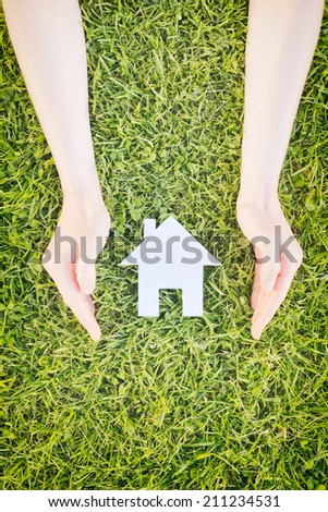 House insurance or safety concept - two hands of a young woman protect a white cutout paper house over grass.