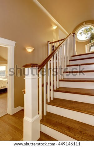 House interior. Hallway with beige walls and wooden staircase with white railings.