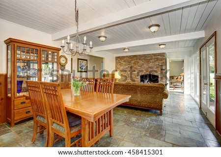 House interior with open floor plan. Dining room with wooden furniture set, living room with brick wall and fireplace. - stock photo