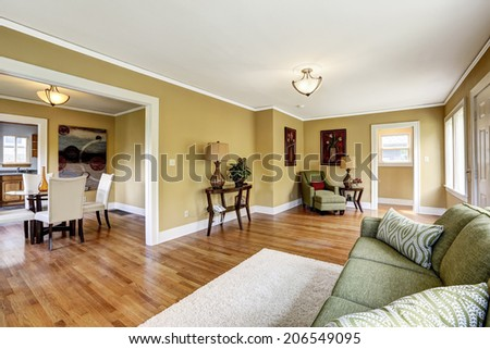 House interior with open floor plan. Room furnished with green sofa and armchair. View of dining table set in kitchen room