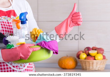 House keeper holding basin full of cleaning supplies and showing thumb up in front of clean kitchen - stock photo