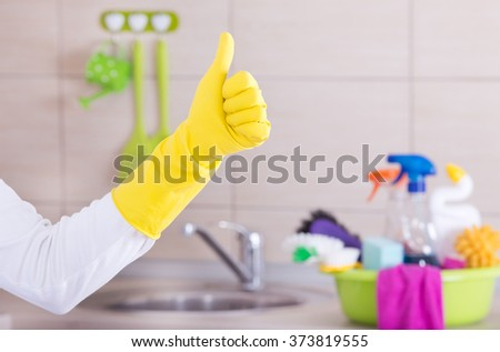 House keeper showing ok sign with thumb up in front of clean kitchen countertop with basin and cleaning supplies in it - stock photo