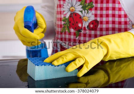House keeper with apron cleaning glass table with sponge and liquid detergent - stock photo
