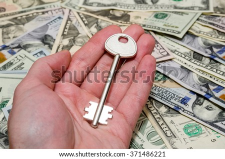 house key above american one hundred dollar bills - stock photo