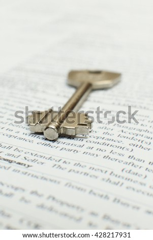 house key lying on a contract of house sale lease insurance or mortgage in a real estate concept viewed low angle with focus to the tip. - stock photo