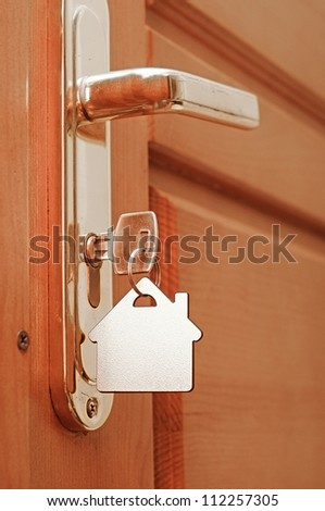 House key on a house shaped keyring in the lock of a door - stock photo