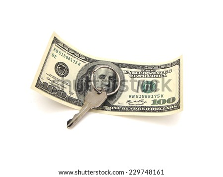 House Key On Ring Resting Upon A United States One Hundred Dollar Federal Reserve Note Over A White Surface.