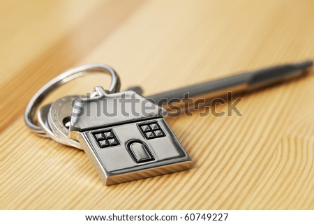 House key on wooden surface - stock photo