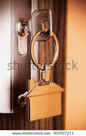 House key with silver chrome pendant with home shape - stock photo