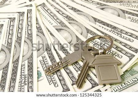 House keys over the hundred dollar banknotes - stock photo
