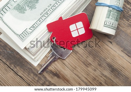 House keys over the hundred dollar banknotes against wooden background  - stock photo