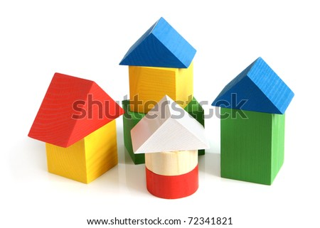House made from children's wooden building blocks on a white background