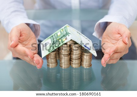 House Made From Stack Of Coins And Banknote Roof - stock photo