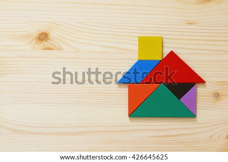 house made from tangram puzzle over wooden table