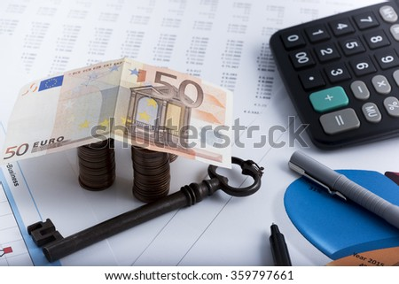 house made of coins and banknote. In the background calculations and histograms - stock photo