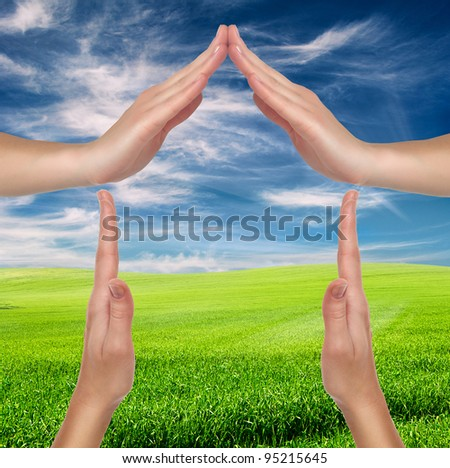 house made of female hands over spring landscape - environment protection concept - stock photo