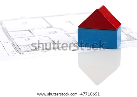 house made of two toy blocks on blueprint of floor plan