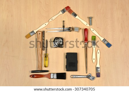 House made out of tools over wooden surface - stock photo