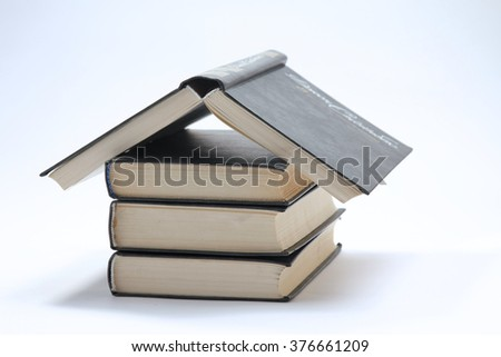 House made with books piled on white background - stock photo