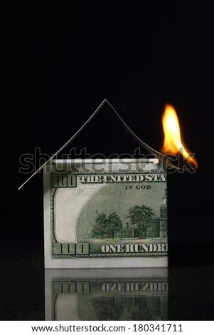 House made with One hundred dollars in fire, burning dollar,  crisis - stock photo