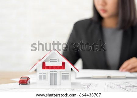 House model on blueprint paper table stock photo royalty free house model on blueprint paper at the table with blurred businesswoman in background real estate malvernweather Image collections