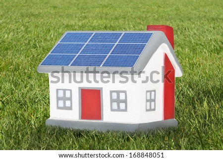 House model plastic with solar panels on meadow - stock photo