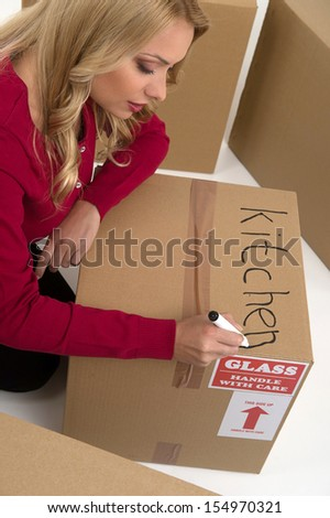 House moving. Top view of young woman writing on the cardboard box  - stock photo