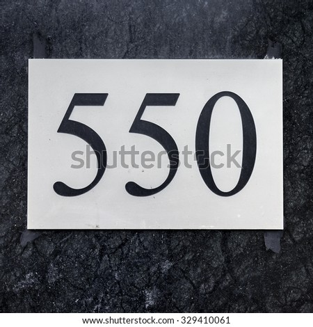 house number five hundred and fifty (550) engraved in a plastic plate. Black numerals on a white background. - stock photo