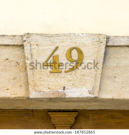 House number forty nine. Brass numerals on a plastered background - stock photo