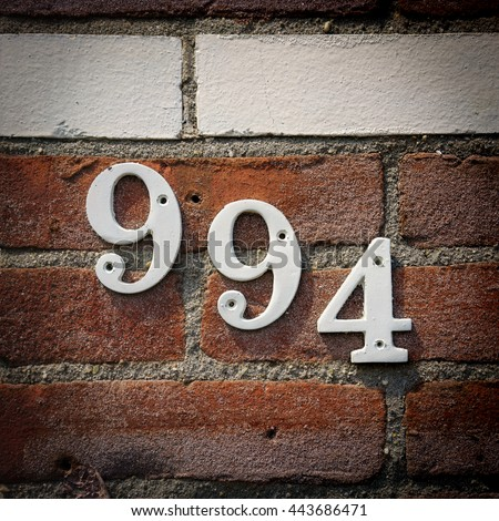 house number nine hundred and ninety four, consistent of three separate numerals. - stock photo