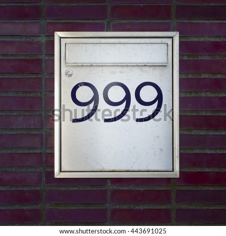house number nine hundred and ninety nine on a metal mailbox - stock photo