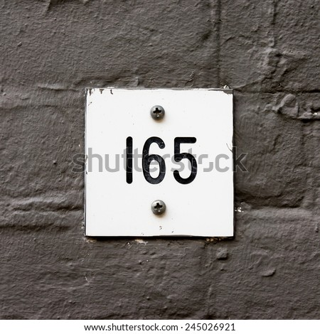 house number one hundred and sixty five, engraved in a plastic plate. - stock photo