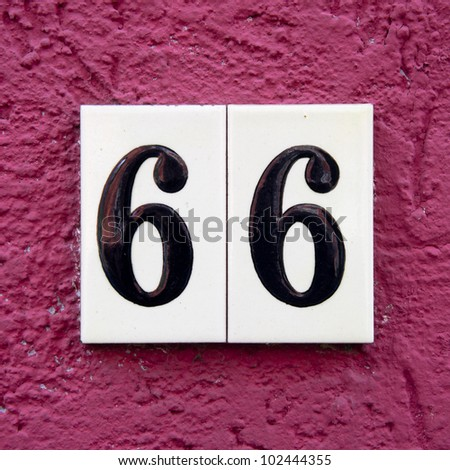 house number sixty-six. Black lettering on ceramic tiles against a pink stucco wall