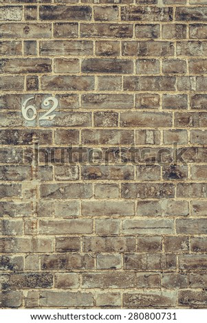 House number 62 sixty two weathered wall closeup - stock photo