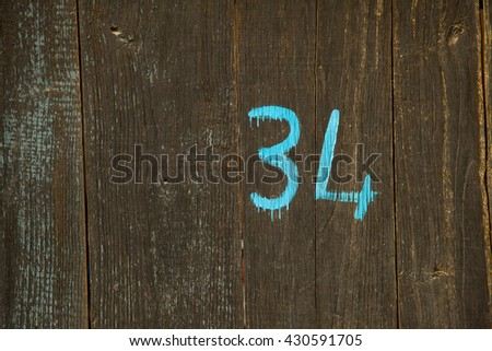 House number 34 thirty four plate on wooden door texture closeup - stock photo