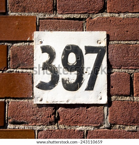 house number three hundred and ninety seven. Black numerals on a white plate - stock photo