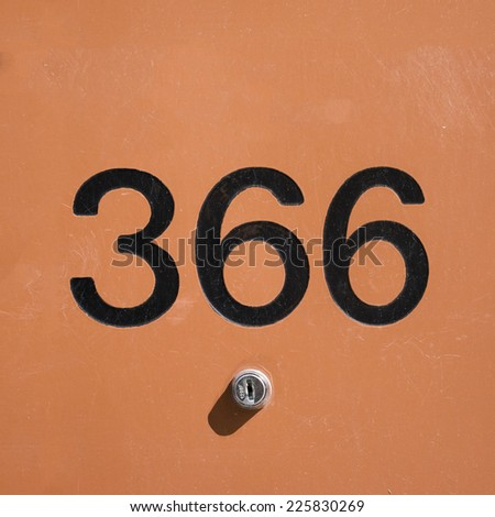 house number three hundred and sixty six, atop a small lock. - stock photo